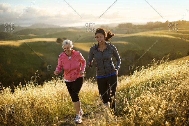 Two women exercising together in a rural landscape.