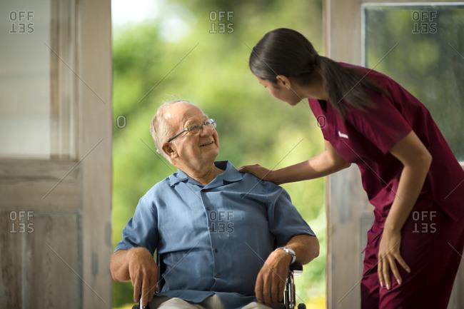 Smiling senior man talking to his young nurse.