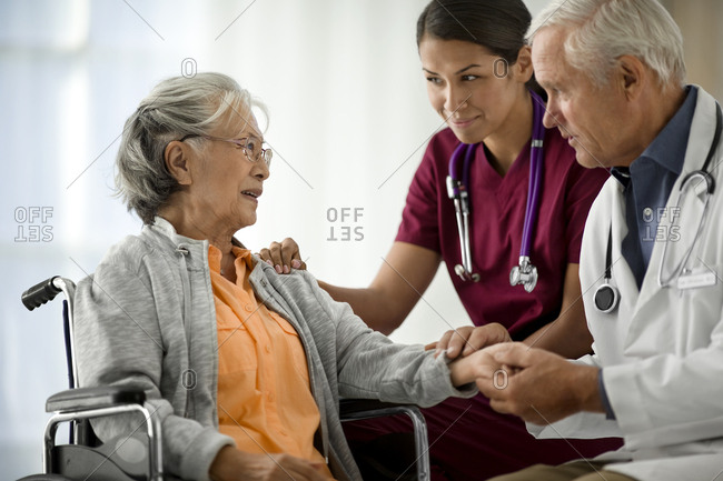 Doctor and nurse speaking to an elderly patient in a wheelchair.