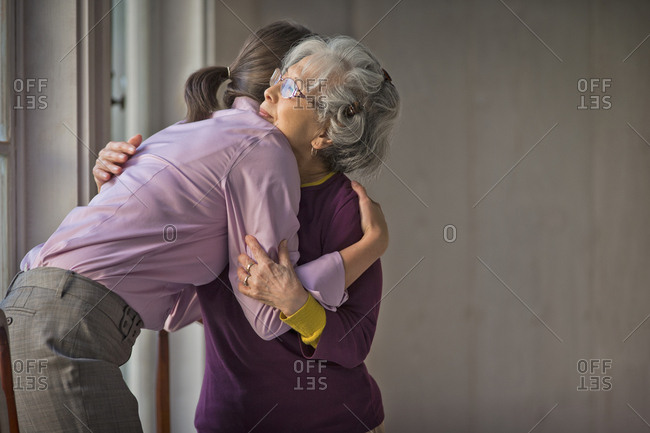 Kind doctor and elderly patient sharing a hug.