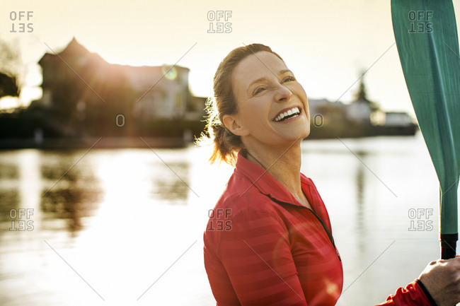 Portrait of a happy paddleboarder holding her oar by a lake.