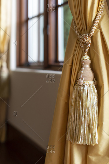 Close up of large tassel on yellow drapes