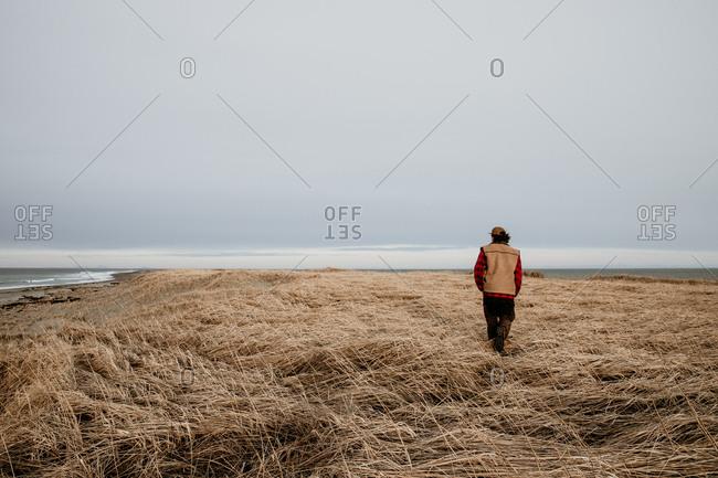 Rear view of man walking through seaside field