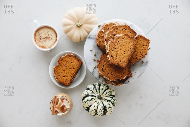 Overhead view of pumpkin bread served with coffee drinks beside small pumpkins