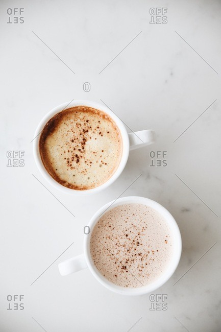 Two frothy lattes on white marble surface