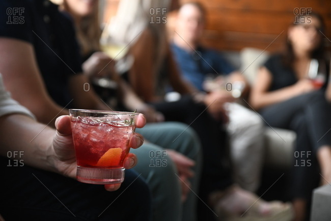 Group of people drinking cocktails with focus on one hand holding a lowball glass