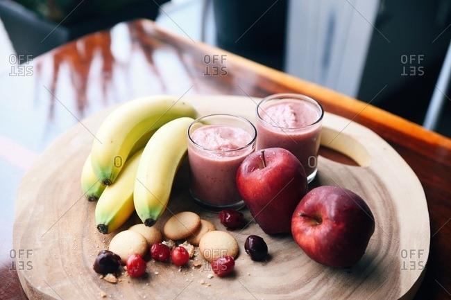 Two smoothies and ingredients on a wooden board
