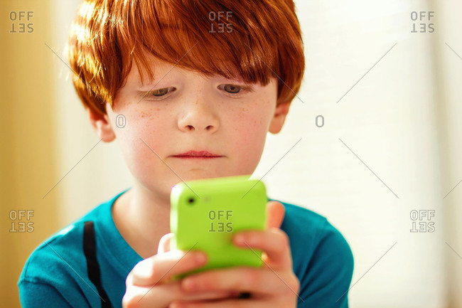 Boy playing game on a mobile phone
