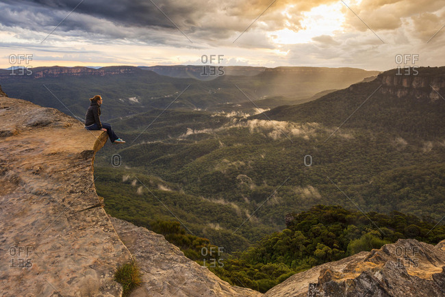 Woman sitting on mountain ledge, Blue Mountains National Park, New South Wales, Australia