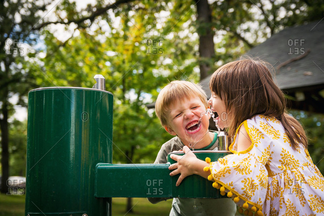 Two children drinking from a water fountain