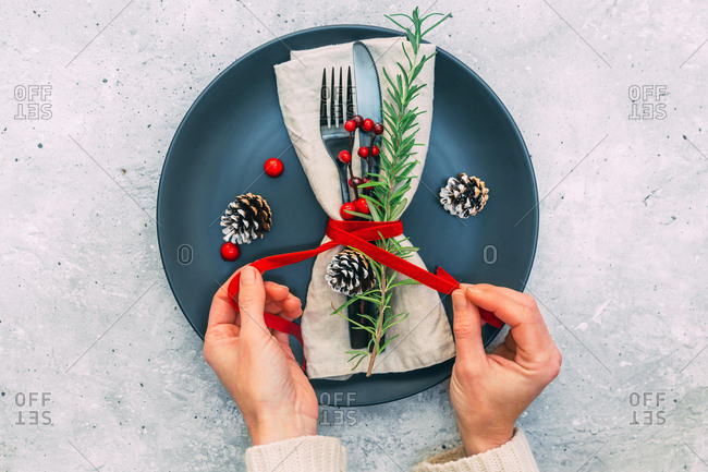 Woman's hands preparing a festive place setting