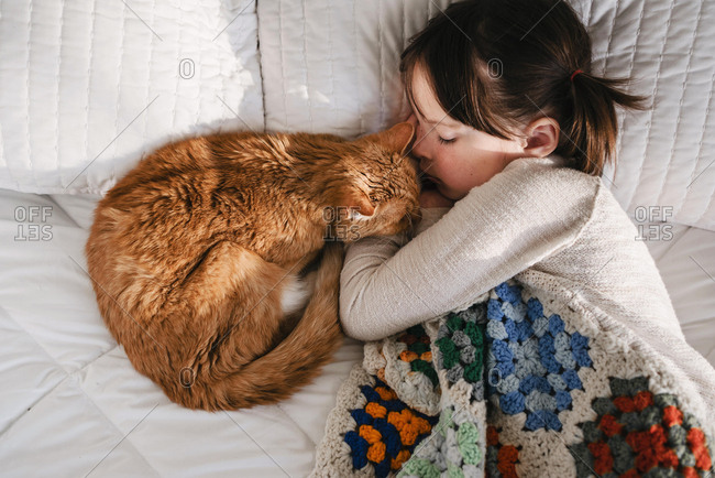 Girl having a nap on a bed with her cat