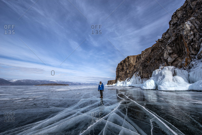 Man standing on frozen Lake Baikal in winter, Siberia, Russia