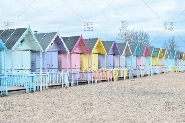 Multi-colored beach huts on beach, Mersea Island, Essex, United Kingdom