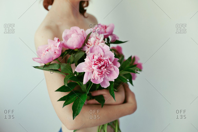 Close-up of a young woman holding a bouquet of peonies