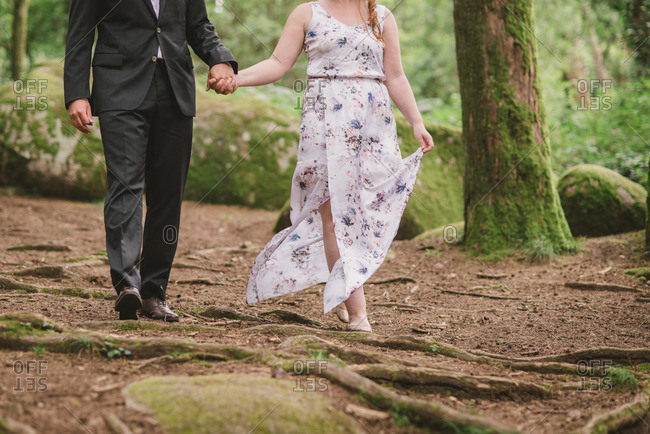 Couple walking hand in hand in the forest after eloping