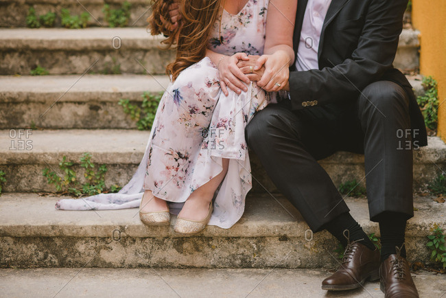 Couple sitting close on concrete steps after eloping