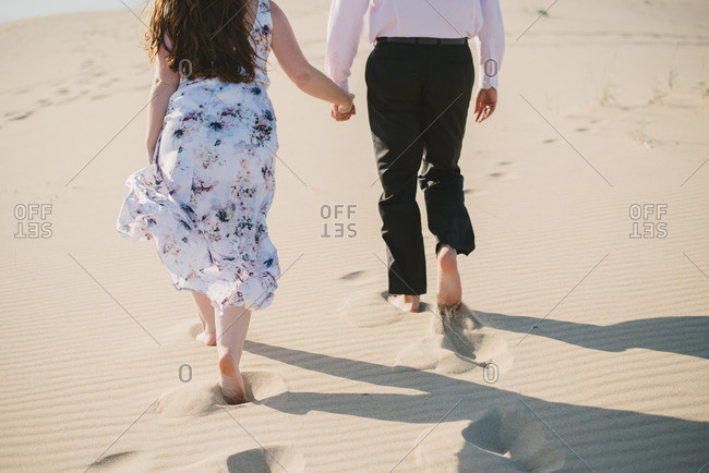 Couple walking hand in hand on the beach after eloping