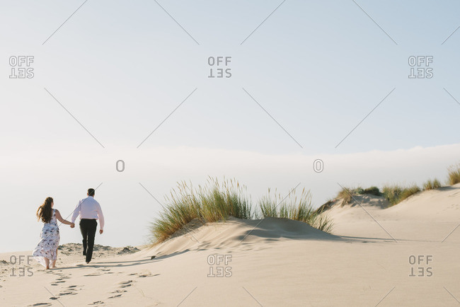 Couple walking hand in hand while eloping on sandy beach