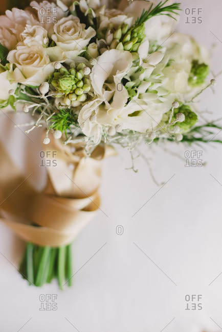 Beautiful floral wedding bouquet wrapped in gold ribbon