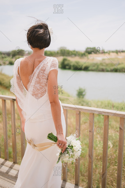 Rear view of bride looking over railing to water