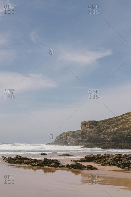 Atlantic Ocean waves rolling into the rocky coast and beach in Alentejo, Portugal