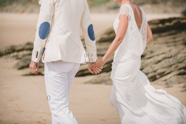 Couple walking hand in hand at their beach wedding