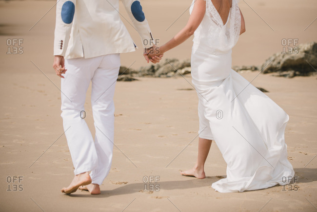 Couple walking hand in hand and barefoot at their beach wedding