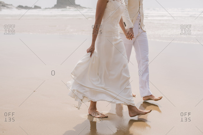Couple holding hands and walking barefoot at their beach wedding