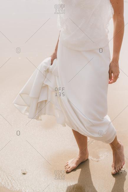 Bride standing barefoot at her beach wedding