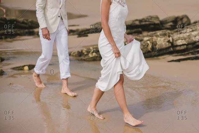 Couple walking barefoot at their beach wedding