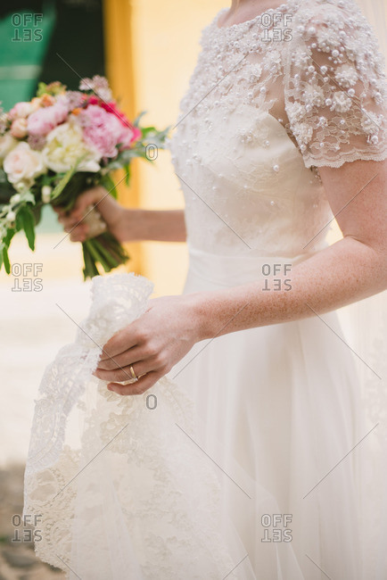 Mid-section of a bride wearing a beautiful white wedding dress