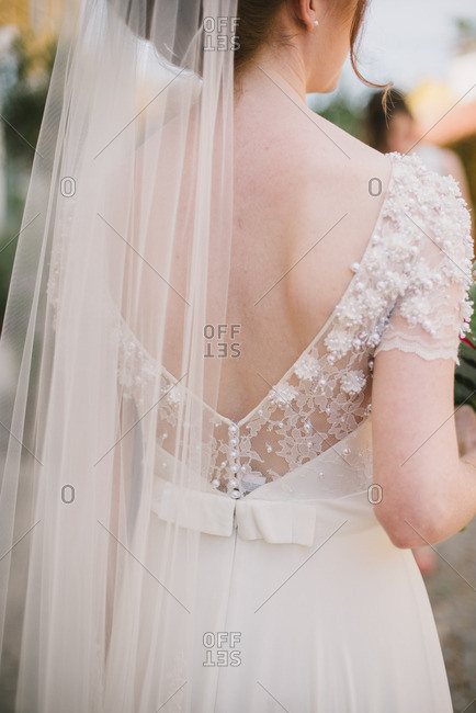 Back view of a bride wearing a beautiful white wedding dress and long veil