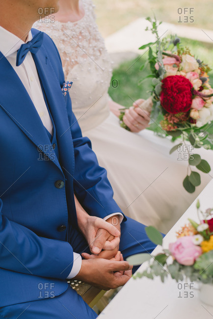 Couple holding hands while sitting at table at their wedding