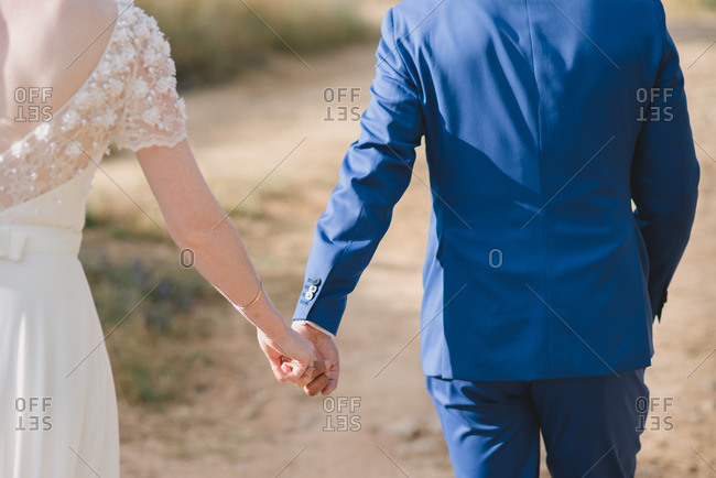 Rear view of a bride and groom walking hand in hand