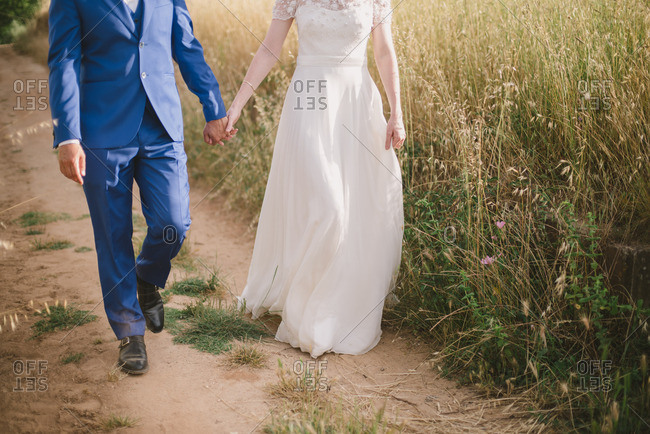 Bride and groom walking hand in hand on dirt path
