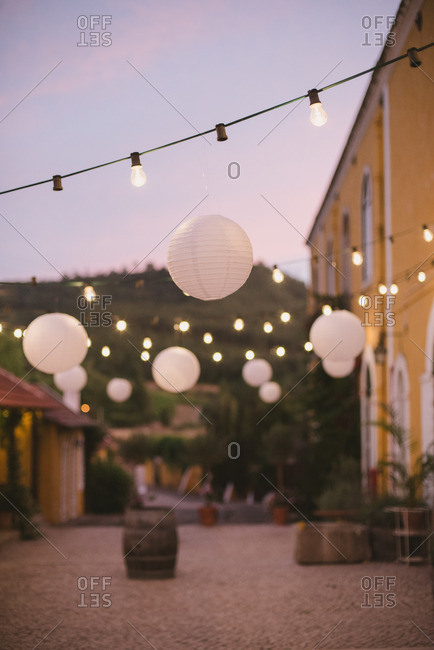 String lights and lanterns hanging from yellow buildings at a rural wine estate in Portugal