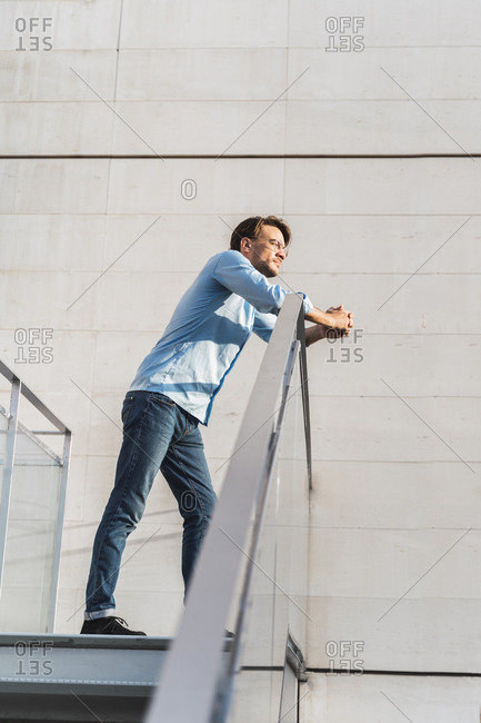 Casual businessman leaning on railing looking away