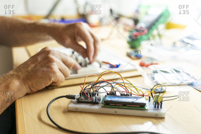 Senior man working on electronic circuits in his workshop