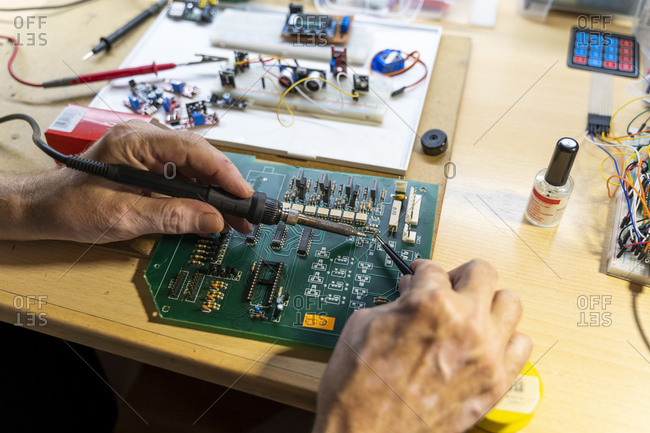 Senior man working on electronic circuits in his workshop- close up