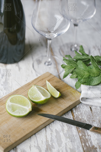 High angle view of lime slices with mint leaves on wooden table