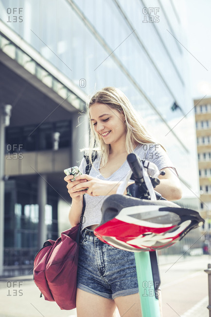 Portrait of smiling young woman  leaning on handlebar of E-Scooter using cell phone- Berlin- Germany