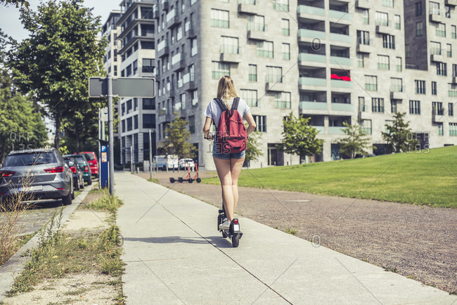 Back view of young woman with backpack riding E-Scooter on pavement- Berlin- Germany