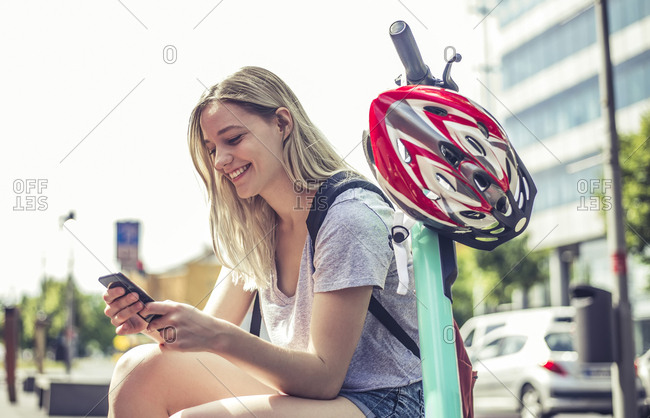 Smiling young woman with E-Scooter looking at cell phone- Berlin- Germany
