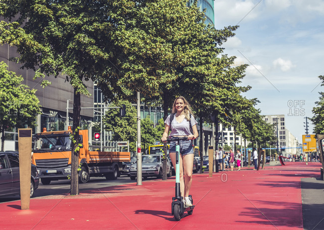 Young woman riding E-Scooter on Boulevard of the Stars- Berlin- Germany