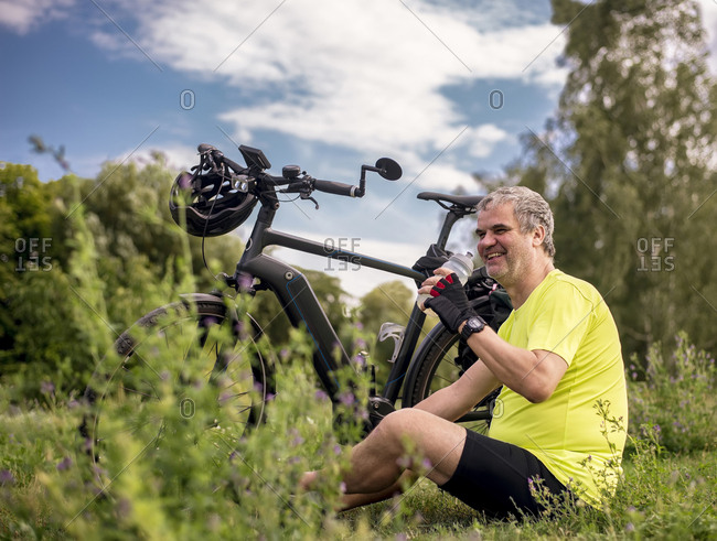 Happy mature man taking a break during his bike tour with an e-bike