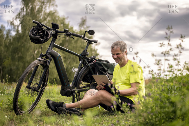 Mature man using digital tablet during his bike tour with an e-bike