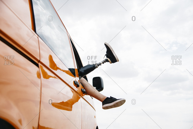 Legs of prosthetic young man dangling out of camper van window