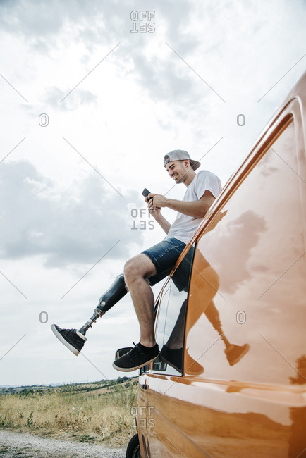 Young man with leg prosthesis sitting on roof of camper van using cell phone
