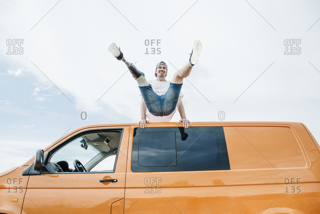 Happy young man with leg prosthesis balancing on roof of camper van